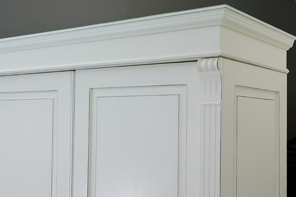Die Profilierungen der Gesimsleiste und Türen geben dem Schrank ein antikes Aussehen