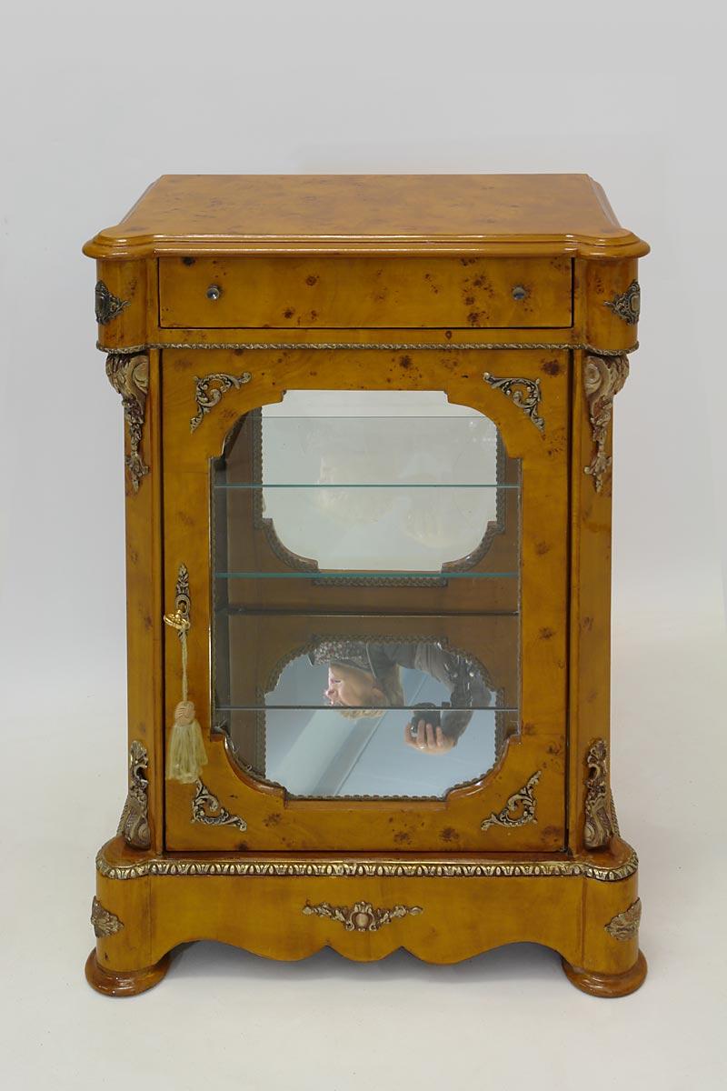 Der Vitrinenschrank ist aus Vogelaugenahorn ähnlichem Holz gefertigt