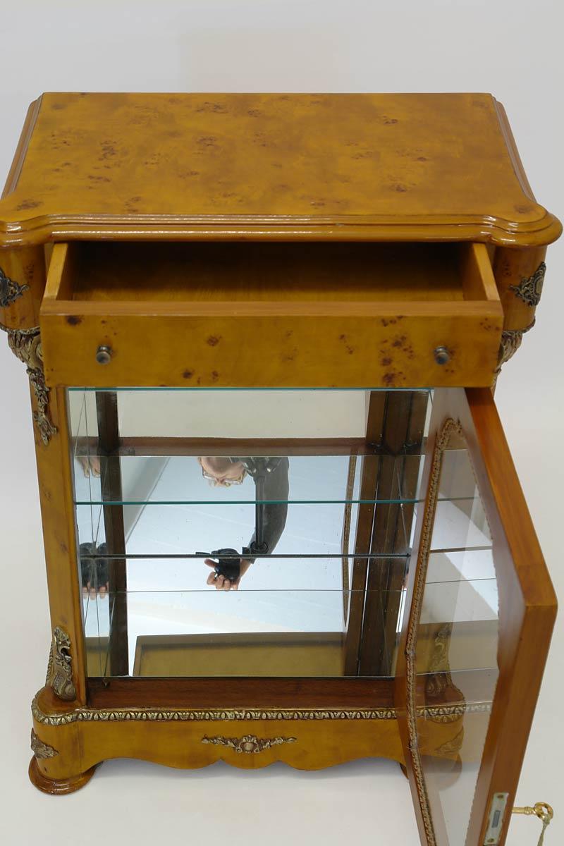 Die Glasvitrine ist mit einer Schublade und einem Glasboden ausgestatttet