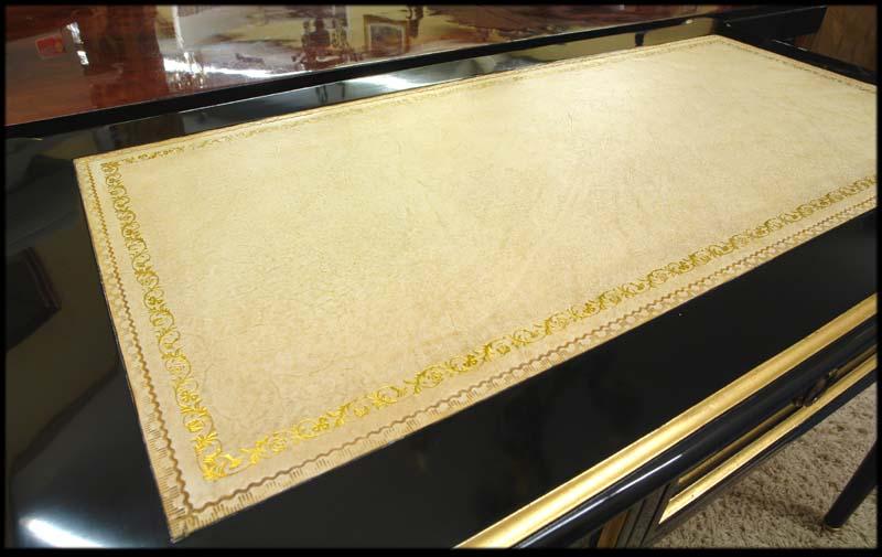 Die Oberfläche wird von einer weißbeige Echtlederauflage geschmückt