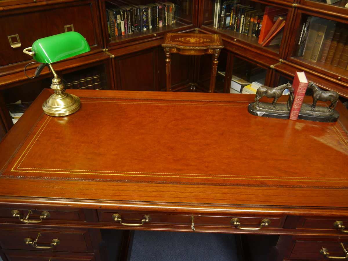 Tischoberfläche mit der Echtlederauflage in rotbraun mit goldfarbener Umrandung.
