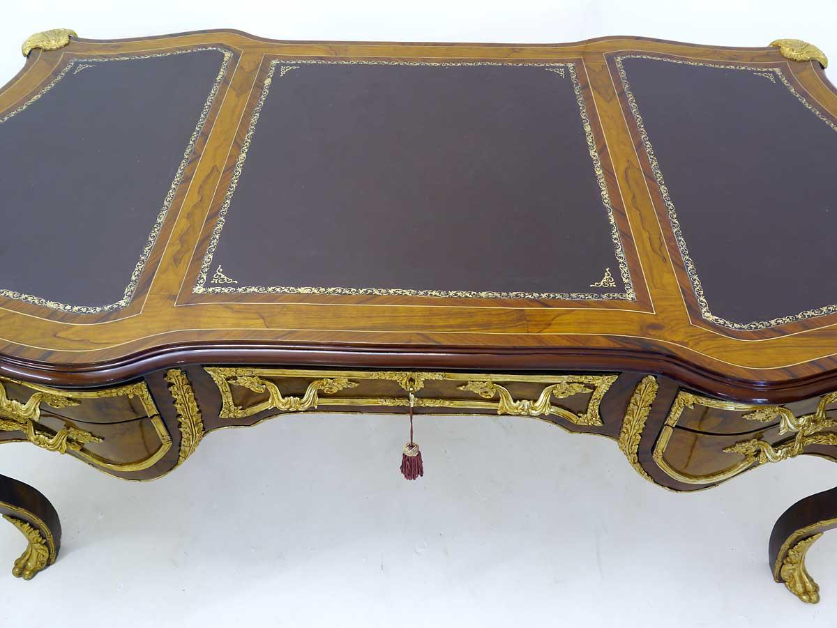 Die Tischoberfläche ist mit braunem Leder bezogen