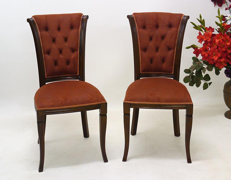 Die Stuhlgruppe ist mit einem rötlichen Bezug aus Alcantara bezogen