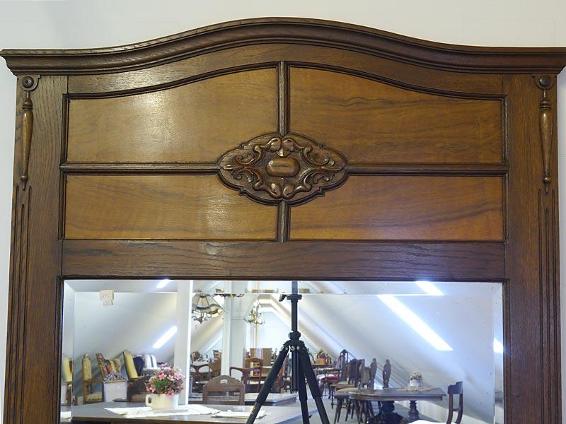 Der Spiegel ist mit ornamentalen und floralen Elementen verziert