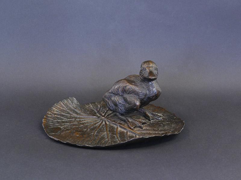 Ente aus Bronze steht auf einem Blatt